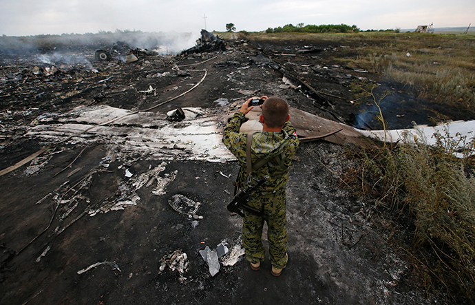 A man takes pictures at the site of a Malaysia Airlines Boeing 777 plane crash, MH17, near the settlement of Grabovo in the Donetsk region, July 17, 2014 (Reuters / Maxim Zmeyev)