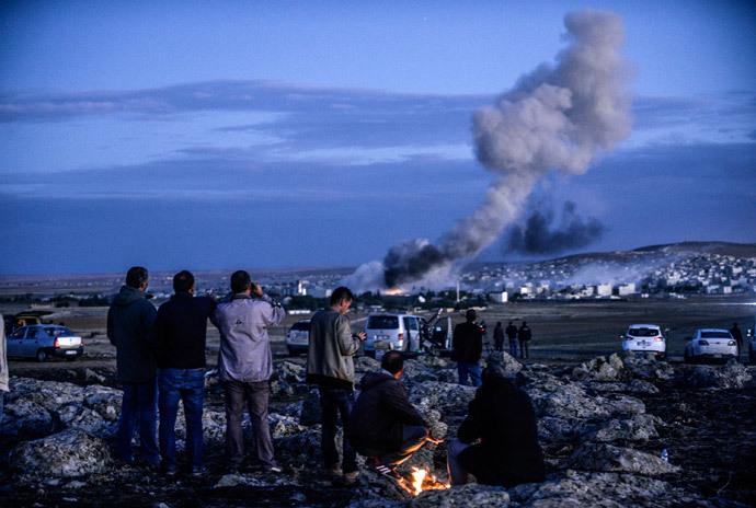 Kurdish people observe smoke rising from the Syrian town of Kobani on October 20, 2014. (AFP Photo / Bulent Kilic)