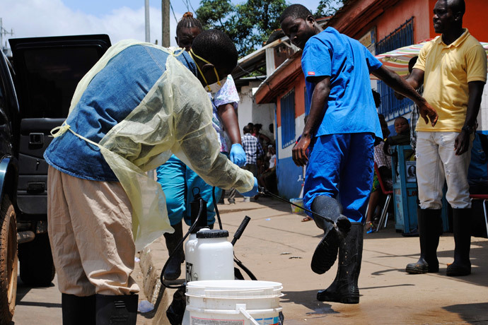 A health worker sprays a colleague's boots with chlorine disinfectant in Monrovia October 20, 2014. (Reuters / James Giahyue)