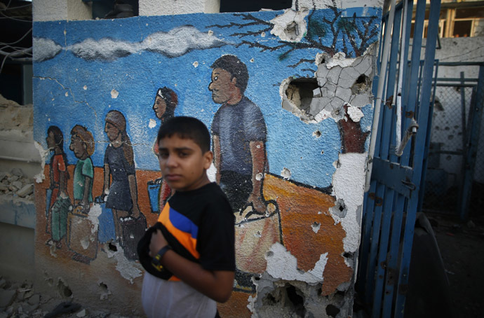 A Palestinian boy looks on as he stands at a United Nations-run school sheltering Palestinians displaced by an Israeli ground offensive, that witnesses said was hit by Israeli shelling, in Jebalya refugee camp in the northern Gaza Strip July 30, 2014. (Reuters/Mohammed Salem)