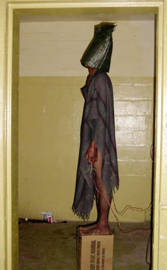 This handout photo from SBS TV received 15 February, 2006 shows a hooded prisoner allegedly being tortured at Iraq's notorious Abu Ghraib jail supposely during interrogation by US soldiers in Baghdad in 2004. (AFP Photo/HO/SBS Dateline)