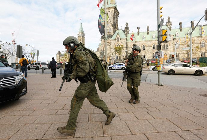 Armed RCMP officers head towards the Langevin Block on Parliament Hill following a shooting incident in Ottawa October 22, 2014.(Reuters / Chris Wattie)