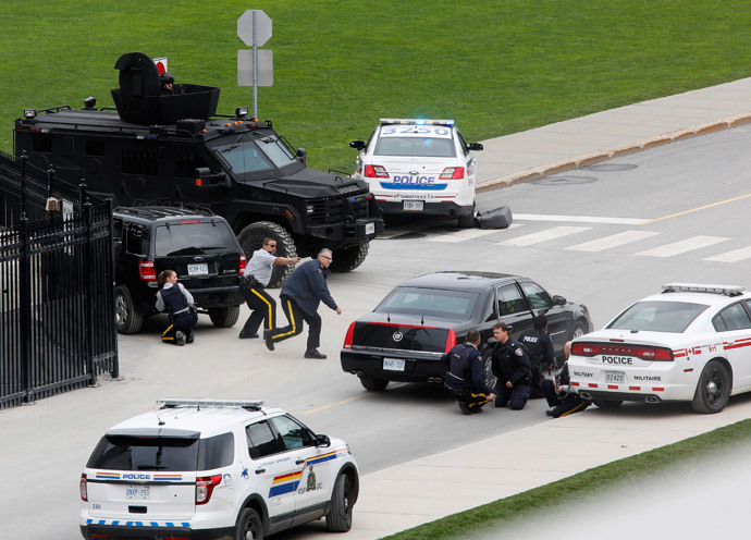 Police officers take cover near Parliament Hill following a shooting incident in Ottawa October 22, 2014.(Reuters / Chris Wattie)