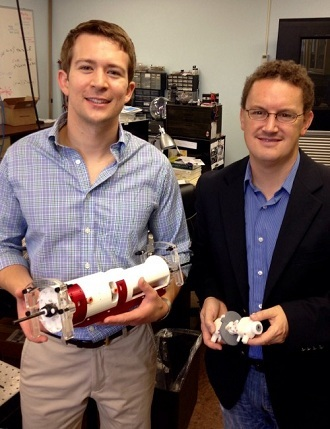 David Comber, left, and Eric Barth holding major components of their surgical robot. (Heidi Hall / Vanderbilt)