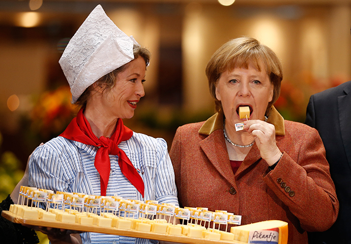 German Chancellor Angela Merkel (R) samples cheese at the pavilion of the Netherlands at the Green Week agricultural fair in Berlin, January 18, 2013 (Reuters / Thomas Peter)