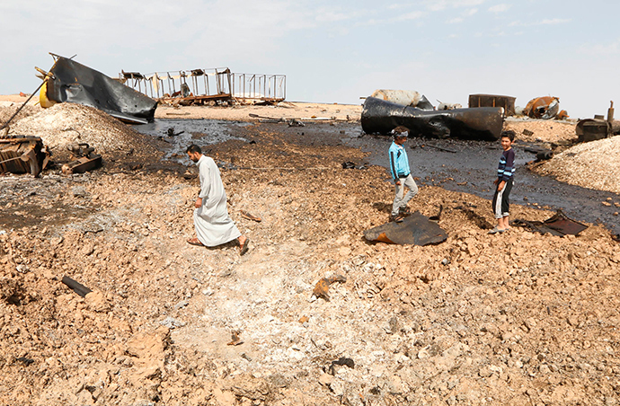 Locals inspect damage at an oil refinery that was targeted by what activists said were U.S.-led air strikes at al-Khaboura village, near the Syrian town of Tel Abyad of Raqqa governate, October 2, 2014 (Reuters / Stringer)