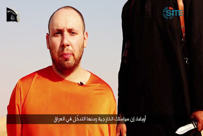 An image grab taken from a video released by the Islamic State (IS) and identified by private terrorism monitor SITE Intelligence Group on September 2, 2014, purportedly shows 31-year-old US freelance writer Steven Sotloff dressed in orange and on his knees in a desert landscape speaking to the camera before being beheaded by a masked militant (R). (AFP Photo / Site Iintelligence Group / HO)