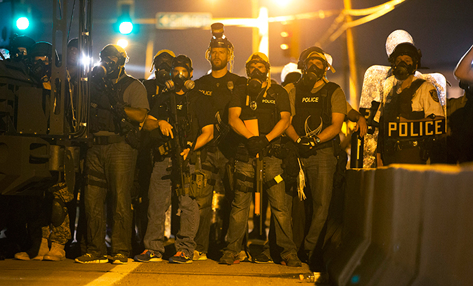 Police officers keep watch while demonstrators (not pictured) protest the death of black teenager Michael Brown in Ferguson, Missouri August 12, 2014 (Reuters / Mario Anzuoni)