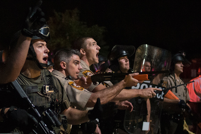 Security forces charge demonstrators after being hit by water bottles during a protest against the shooting of unarmed black teen Michael Brown in Ferguson, Missouri August 20, 2014 (Reuters / Adrees Latif)