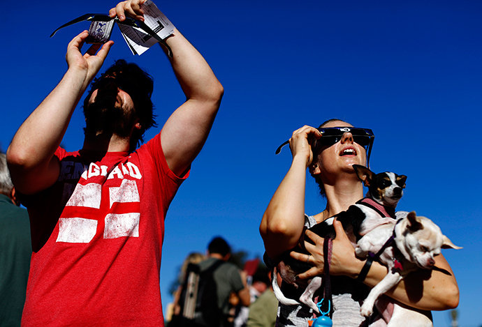 Angie Henderson holds her Chihuahua dogs as she looks up to view a partial solar eclipse outside the Reuben H. Fleet Science Center in San Diego, California October 23, 2014 (Reuters / Mike Blake)