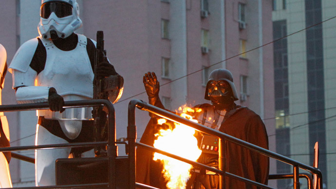 """A candidate (R), presenting himself in the character of """"Star Wars"""" villain Darth Vader and representing the Internet Party of Ukraine which runs for parliament, stands on the top a vehicle as he leaves after a meeting with his supporters and voters in Kiev, October 22, 2014.(Reuters / Valentyn Ogirenko )"""