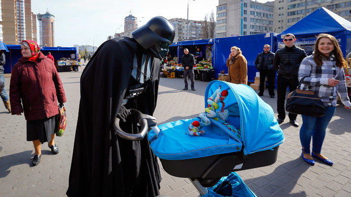 """""""Darth Vader"""", the leader of the Internet Party of Ukraine, looks at a child in a pram at a street market near the Ukrainian Central Elections Commission in Kiev April 3, 2014.(Reuters / Shamil Zhumatov)"""