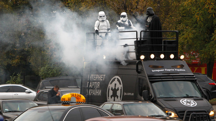"A candidate (R), presenting himself in the character of ""Star Wars"" villain Darth Vader and representing the Internet Party of Ukraine which runs for parliament, stands on the top a vehicle as he leaves after a meeting with his supporters and voters in Kiev, October 22, 2014.(Reuters / Valentyn Ogirenko)"