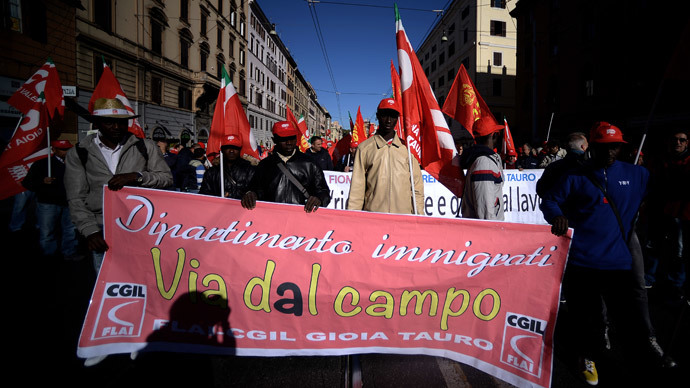 "Immigrant farmers hold a banner reading ""away from the field"" during a demonstration organised by Italian General Confederation of Labour (CGIL) union on October 25, 2014 in central Rome.(AFP Photo / Filippo Monteforte)"