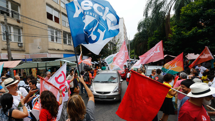 Supporters of Brazil's presidential candidates Aecio Neves (Blue) of Brazilian Social Democratic Party (PSDB) and Dilma Rousseff (red) of Workers Party (PT) cheer ahead of Sunday's election runoff at a weekly street market in Rio de Janeiro October 25, 2014.(Reuters / Ricardo Moraes )