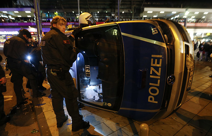 German riot police officers use torches to look for their personal belongings in an overturned police van following a demonstration by German far-right groups in Cologne October 26, 2014. (Reuters/Wolfgang Rattay)