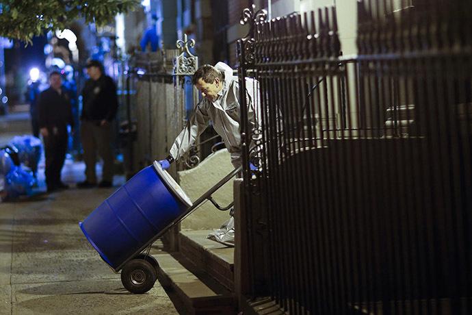 """Um membro de uma equipe de limpeza com """"Bio Recovery Corporação"""" vestindo equipamentos de proteção individual (EPI) empurra um barril para ser carregado em um caminhão de Centros de Controle e Prevenção de Doenças (CDC), após a limpeza do apartamento onde o Dr. Craig Spencer vive em Nova Iorque 24 de outubro de 2014. (Reuters / Eduardo Munoz)"""