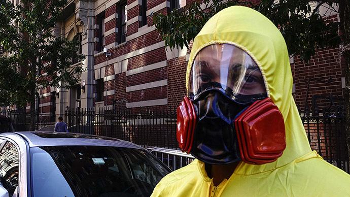 Um homem vestindo equipamentos de proteção individual (EPI) como um traje de Halloween, fica na frente do prédio onde o Dr. Craig Spencer vive em Nova York 25 de outubro de 2014. (Reuters / Eduardo Munoz)