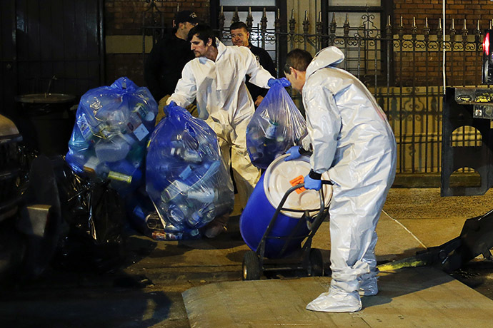 "Members of a cleaning crew with ""Bio Recovery Corporation"" wearing personal protective equipment (PPE) push a barrel to be loaded in a truck of Centers for Disease Control and Prevention (CDC) after cleaning the apartment where Dr. Craig Spencer lives in New York October 24, 2014. (Reuters/Eduardo Munoz)"