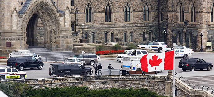 Armed RCMP officers approach Centre Block on Parliament Hilll following a shooting incident in Ottawa October 22, 2014. (Reuters/Chris Wattie)