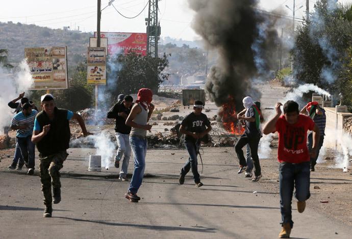 Palestinians run to take cover from tear gas fired by Israeli security forces during clashes following the funeral of Palestinian-American Orwa Hammad on October 26, 2014 in the West bank village of Silwad, near Ramallah. (AFP Photo / Abbas Momani)