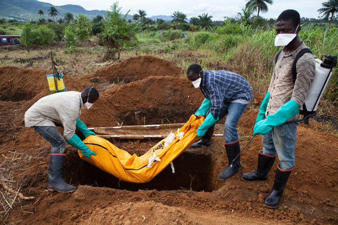 Volunteers in protective suit burry the body of a person who died from Ebola in Waterloo, some 30 kilometers southeast of Freetown (AFP Photo / Florian Plaucheur)