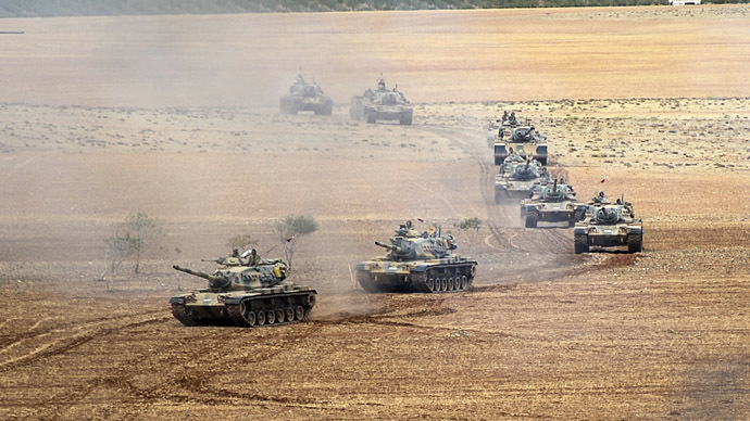 Turkish Army tanks take position as they turn towards the Syrian city of Kobani on September 29, 2014 in Suruc after three mortars hit the Turkish side. (AFP Photo/Bulent Kilic)