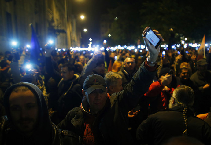 People hold up their mobile phones as they protest against a new tax on Internet data transfers in the centre of Budapest, October 28, 2014. (Reuters/Laszlo Balogh)