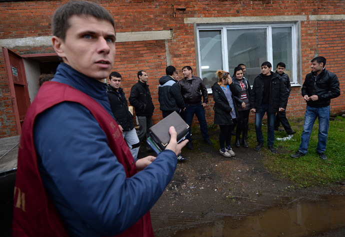 An officer of the Federal Migration Service, left, holds documents of foreign workers during a raid conducted by the Federal Migration Service to identify illegal migrants (RIA Novosti/Maksim Blinov)