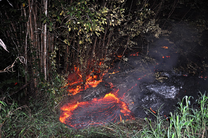 This October 28, 2014 image provided by the US Geological Survey(USGS) shows the lava flow eminating from the KÄ«lauea volcano in Hawaii moving through thick vegetation near the Pahoa cemetery. (AFP Photo)