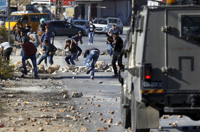 Palestinian youths from the Jalazoun refugee camp clash with Israeli security forces on a road at the entrance of the Jewish West Bank settlement of Beit El, north of Ramallah, following a march by Palestinian demonstrators against Israeli restrictions on the Al-Aqsa mosque and against Jewish settlements in the West Bank on October 24, 2014 (AFP Photo)