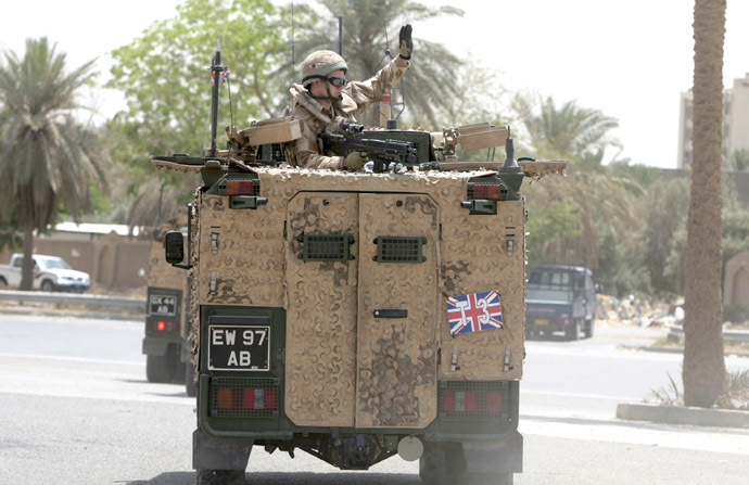 "A British soldier waves as he rides in a military vehicle along the parade ground in Baghdad's fortified ""Green Zone"" on May 16, 2009. (AFP Photo)"