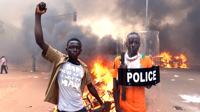 Protesters pose with a police shield outside the parliament in Ouagadougou on October 30, 2014 as cars and documents burn outside. (AFP Photo/Issouf Sango)