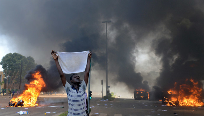 A protester holds a white cloth as cars and documents burn outside the parliament in Ouagadougou on October 30, 2014. (AFP Photo/Issouf Sango)