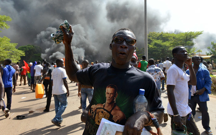 Protesters stand outside the parliament in Ouagadougou on October 30, 2014 as cars and documents burn outside. (AFP Photo/Issouf Sango)