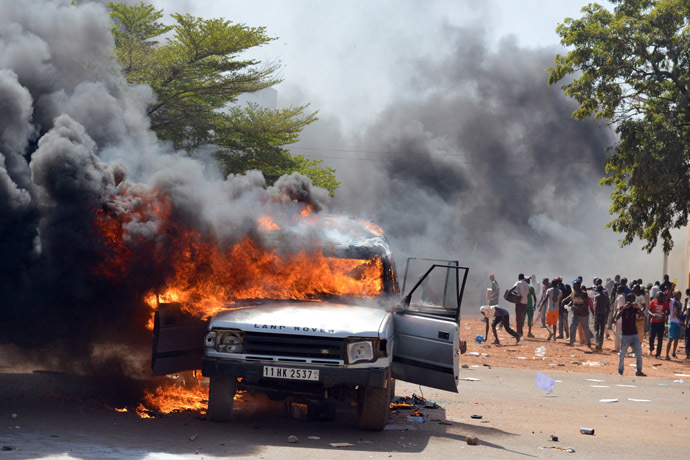 Cars and documents burn outside the parliament in Ouagadougou on October 30, 2014. (AFP Photo/Issouf Sango)