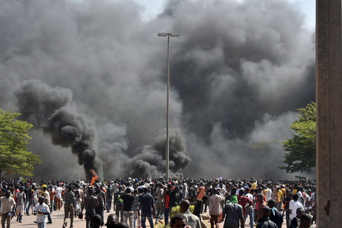 People stand in front of smoke rising from the Burkina Faso's Parliament, where demonstrators set cars on fire parked in a courtyard of the Parliament, on October 30, 2014 in Ouagadougou, as they protest at plans to change the constitution to allow President Blaise Compaore to extend his 27-year rule. (AFP Photo/Issouf Sango)