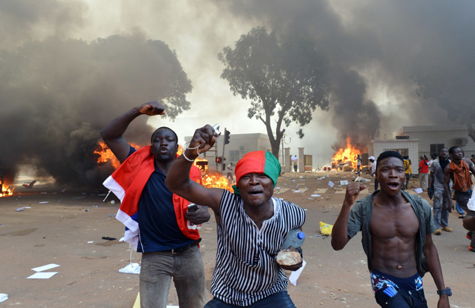 Men shout slogans in front of burning cars, near the Burkina Faso's Parliament where demonstrators set fire, on October 30, 2014 in Ouagadougou, as they protest against plans to change the constitution to allow President Blaise Compaore to extend his 27-year rule. (AFP Photo/Issouf Sango)