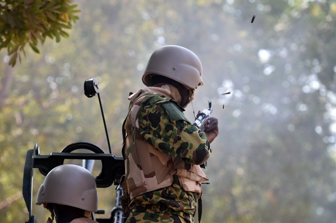 Burkina Faso troops shoot in the air to try to disperse protesters outside the parliament in Ouagadougou on October 30, 2014 as cars and documents burn. (AFP Photo/Issouf Sango)