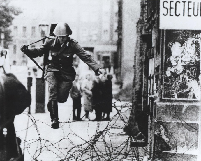 Conrad Schumann escaping across the barbed wire (Image from flickr.com/The Central Intelligence Agency)