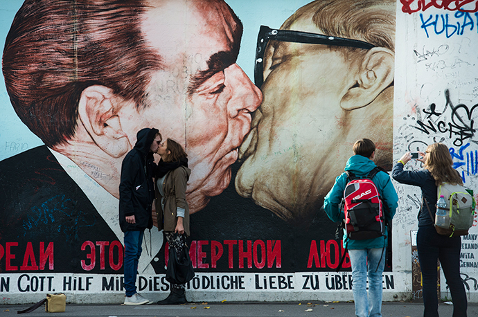 Tourists mimic a kiss in front of a likeness of that between then-Soviet leader Leonid Brezhnev (L) and East Germany's Erich Honecker at the East Side Gallery, a stretch of the Berlin wall, in Berlin (AFP Photo / John Macdougall)
