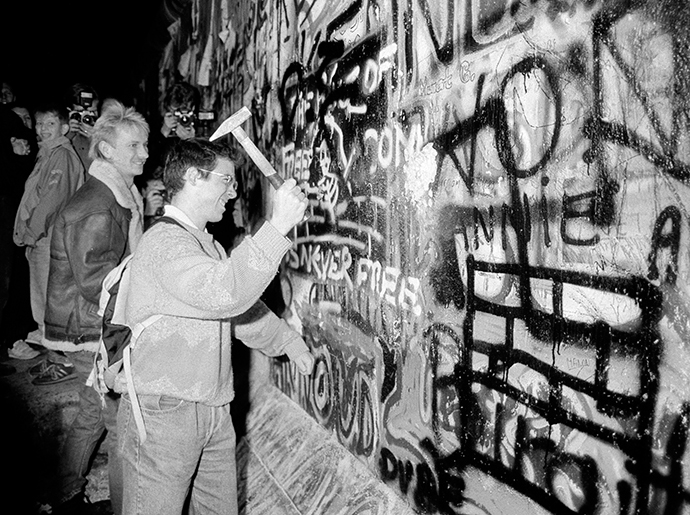 A man hammers a section of the Berlin Wall near the Brandenburg Gate after the border opening was announced, November 9, 1989. (Reuters / Fabrizio Bensch)