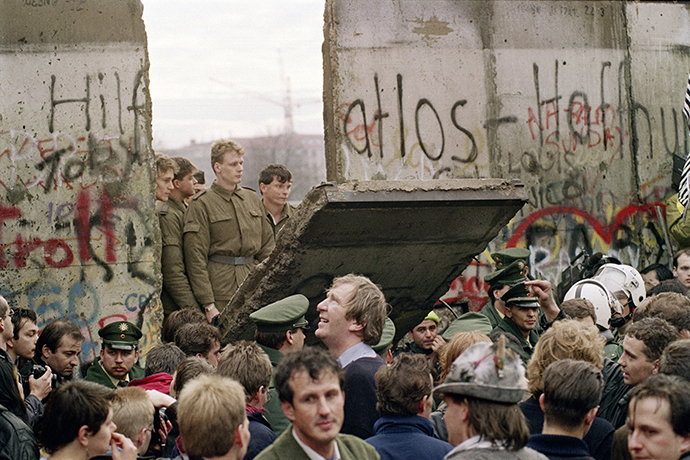 November 11, 1989. West Berliners crowd in front of the wall watching East German border guards demolish a section to open a new crossing point between East and West Berlin, near the Potsdamer Platz. (AFP Photo / Gerard Malie)