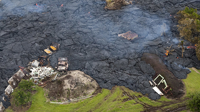 Burning debris can be seen in the lava flow from Mount Kilauea that is inching closer to the village of Pahoa, Hawaii October 29, 2014. (Reuters/Marco Garcia)