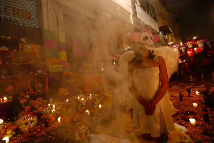 Sex workers wear skeleton masks, a traditional Mexican symbol representing the Day of the Dead, as they make an offering during a procession to remember their deceased colleagues, especially those who were violently murdered, in Mexico City (Reuters / Edgard Garrido)