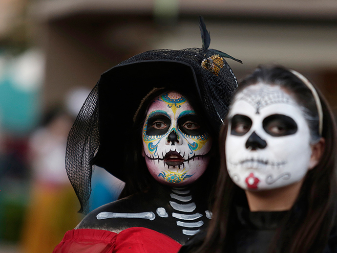 """Women with faces painted to look like the popular Mexican figure called """"Catrina"""" are seen in Zapopan (Reuters / Alejandro Acosta)"""