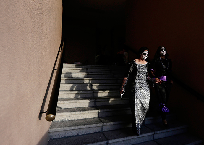 """Women with faces painted to look like the popular Mexican figure called """"Catrina"""" walk down a staircase in Zapopan (Reuters / Alejandro Acosta)"""