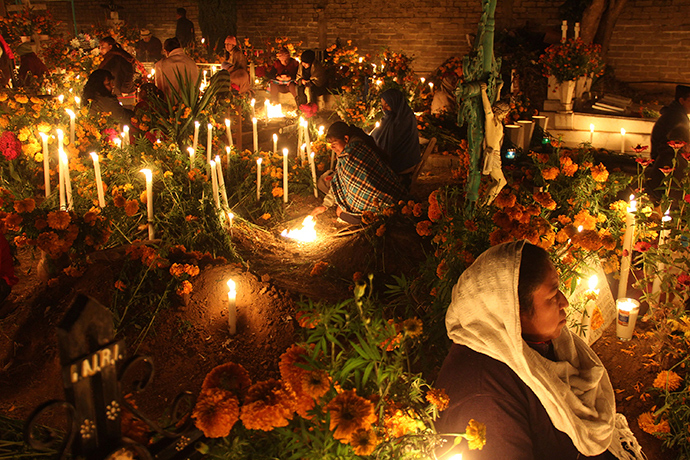 Women sit next to the graves of their relatives on the Day of the Dead, at a cemetery in Santa Maria Atzompa, on the outskirts of Oaxaca (Reuters / Jorge Luis Plata)