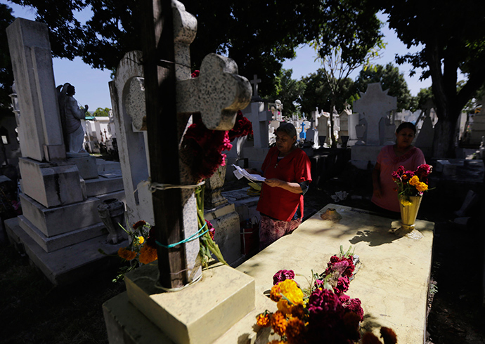 Women pray at the grave of a relative at the municipal cemetery during the Day of the Dead, in Iguala in the southwestern state of Guerrero (Reuters / Henry Romero)