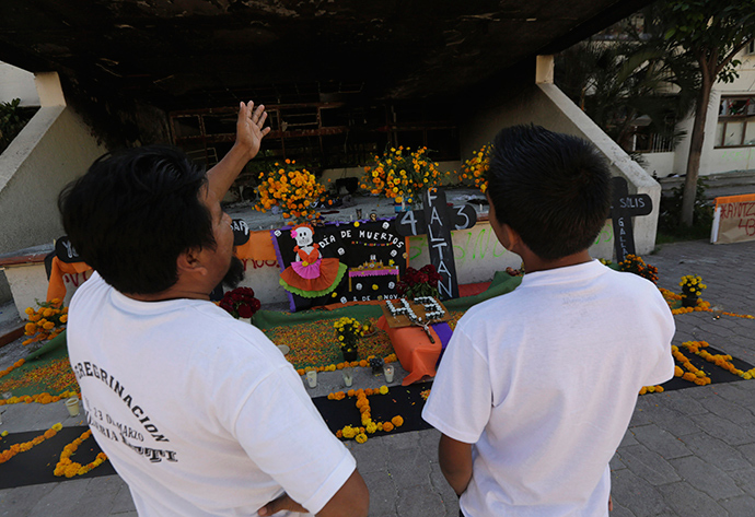 People look at an installation of a skeleton, skulls and Cempasuchil marigold petals, part of an altar assembled by residents to celebrate the Day of the Dead, outside the Municipal Palace in Iguala, in the southwestern state of Guerrero (Reuters / Henry Romero)
